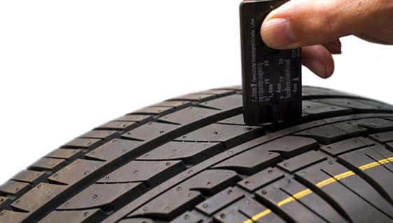 Checking the tire tread depth with a tread depth gauge